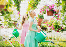 Two rustic girls in the green house Stock Images