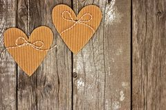 Two rustic heart shaped gift tags against wood Royalty Free Stock Photos