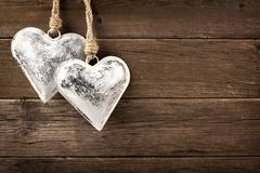 Two rustic metal heart ornaments hanging on wood. Two rustic metal heart ornaments hanging against a vintage wooden background stock photo