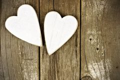 Two rustic white wooden hearts on old wood background Stock Photos