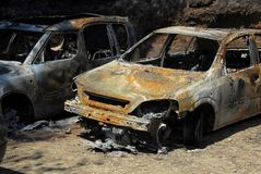 Two rusty burned out cars. Two rusty completely burned out ruined cars after forest fire royalty free stock image
