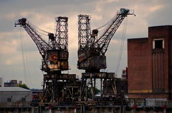 Two rusty cranes stock images