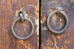 Two rusty iron ring door knobs over an old wooden door Stock Image