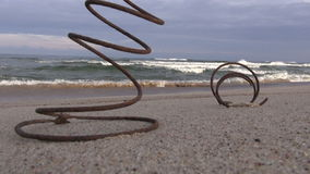 Two rusty metal spring on beach sand and waves. Two old rusty metal spring on ocean beach sand and waves stock video