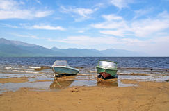 Two rusty motor boats at anchor on the beach at the shores of La Stock Photo