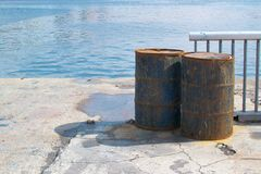 Two rusty old industrial drums on the banks of a river Royalty Free Stock Images