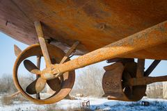 Two rusty screws in the nozzle belonging to the ship, which stands in a dry dock in winter.  stock image
