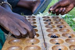 Two Rwandan Men`s Hands Shown Playing a Local Board Game Called Igisoro. With Black Pebbles. East African Culture stock image