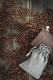 Two sacks of roasted arabica coffee beans. On a dark wooden background top view Stock Images