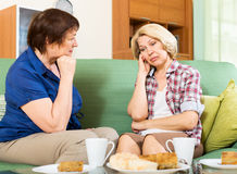 Two sad aged women chating on couch Royalty Free Stock Images