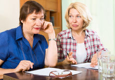 Two sad aged women with documents Stock Images