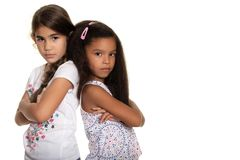 Two sad and angry small girls on a white background. Two sad and angry small girls - Isolated on white royalty free stock photography