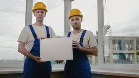 Two sad builders with boardsheet or poster looking for a job. Medium shot.Two sad builders with boardsheet or poster looking for a job. Professional shot in 4K stock video