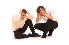 Two sad businessmen. Sitting on the floor. isolated on white Royalty Free Stock Images