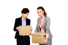 Two sad businesswoman carrying box. Royalty Free Stock Photography