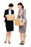 Two sad businesswoman carrying box. Stock Images
