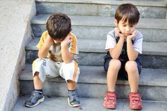 Two sad children. On steps Royalty Free Stock Photo