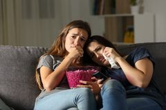 Two sad friends crying watching tv in the night. Sitting on a couch in the living room at home Royalty Free Stock Image