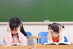Two sad girls doing in homework Stock Photo