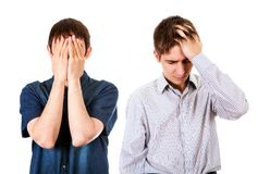 Sad Young Guys. Two Sad Guys close the Faces on the White Background Royalty Free Stock Photography