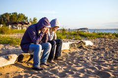 Two Sad Guys outdoor. Two Sad Men sit on the Log at the Seae royalty free stock photography