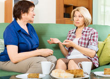 Two sad mature women chating on couch. At home stock photography