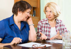 Two sad mature women with documents Stock Photography