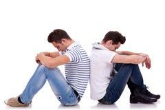 Two sad men sitting back to back stock image