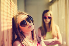 Two sad  teenage girls wearing sunglasses in Stock Photos