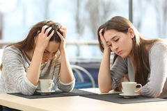 Two sad women in a coffee shop Royalty Free Stock Images