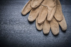 Two safety gloves on dark wooden board Stock Photos