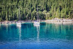 Two sailboats anchored in an emerald bay stock photo