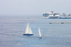 Two Sailboats and Cruise Ships Stock Photo