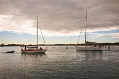 Two Sailboats with furled sails meeting on Australian lake. SWANSEA, NEW SOUTH WALES, AUSTRALIA, JULY 11 2017: Two Sailboats with furled sails meeting on the Royalty Free Stock Photography