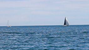 Two Sailboats On Lake Michigan One Under Sail The Other Motoring stock video footage