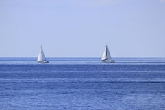 Two sailboats on open sea horizon Royalty Free Stock Photography