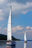 Two sailboats. On peaceful still waters in a harbor royalty free stock photos
