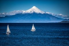 Two sailboats sail in front of snow capped Orsono Volcano in Chile. In South America stock images