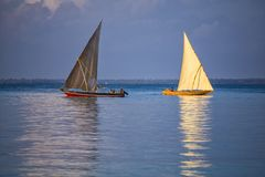 Two sailboats on the water surface. Zanzibar island , Tanzania, Africa. Ancient wooden sailing boats with people on board on the sea surface at the morning stock photography