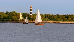 Two sailing boats fly by the canal along the lighthouse. Royalty Free Stock Image