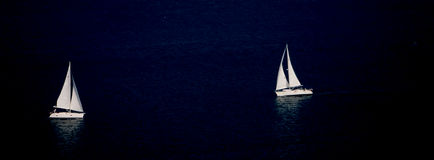 Two Sailing Boats at Night. Two Boats Sailing in Opposite Directions at Night on a very dark Ocean Royalty Free Stock Images
