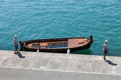 Two sailors men and the boat at the deep-green wharf in Split stock images