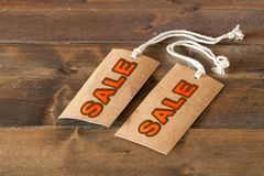 Two sale labels on a wooden table. Rad letters and string on the labels Royalty Free Stock Photo