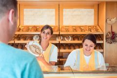 Two salesladies selling bread and other products in bakery shop. Working as a team stock photo