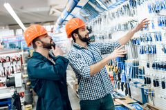 Two salesmen are checking equipment selection in power tools store. Two salesmen in blue robe and checkered shirt are checking equipment selection in power stock photo