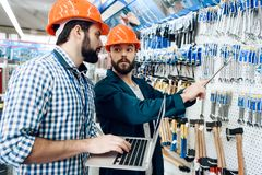 Two salesmen are checking equipment selection in power tools store. Two salesmen in construction helmets are checking equipment selection in power tools store stock photo