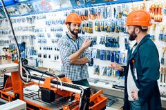 Two salesmen are discussing equipment selection near woodworking machine in power tools store. Two salesmen in construction helmets are discussing equipment royalty free stock image