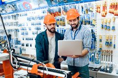Two salesmen are discussing equipment selection near woodworking machine in power tools store. Two salesmen in construction helmets are discussing equipment stock photo
