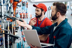 Two salesmen are checking tooks inventory with laptop in power tools store. Two salesmen in red shirt and baseball cap and blue robe are checking tooks royalty free stock photography
