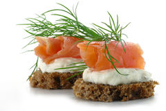 Two  salmon canapes with fresh dill garnish, isolated on white b Royalty Free Stock Photos